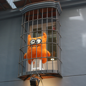 Stuffed monster in a cage over a shop window in Spain
